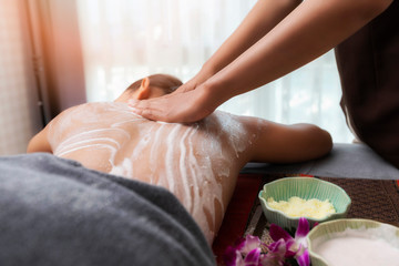 Spa therapist applying scrub salt and cream on young woman back at salon spa. Hands massaging female back with scrub.