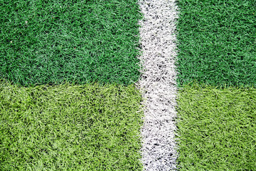 Green artificial grass football field. Half line in the middle of the football field. View from top side field.