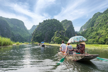 Activity downstream in mountain valley on boat with vietnamese using foot paddle Fototapete