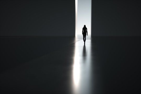 Silhouette of woman goes on abstract way through light
