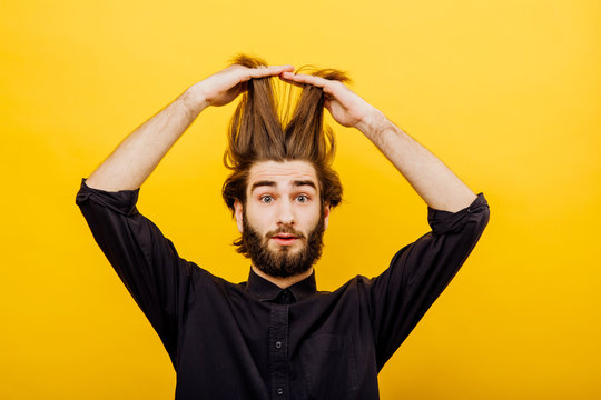 man pulls his hair up, raises long hair up, is surprised, I look healthy. isolated on yellow background, facial expression positive
