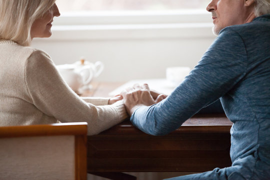 Cropped image middle aged couple sitting at table holding hands