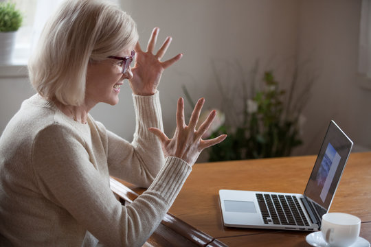 Angry middle aged woman having difficulties with computer
