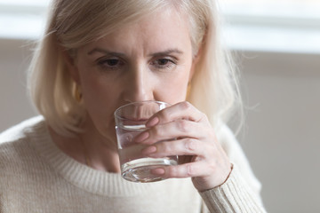 Close up portrait aged woman drinking still water
