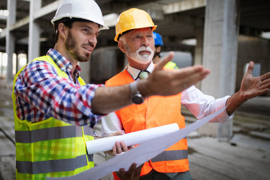 Team of architects and engineer in group on construciton site check documents and business workflow