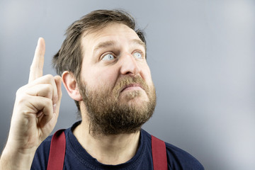 bearded man lifted his finger up and looks up, gray background