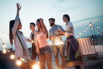 Carefree group of happy friends enjoying party on rooftop terrace Wall mural