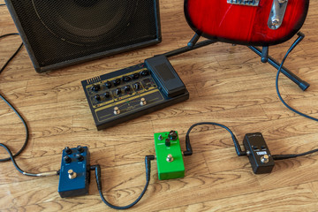 Setting up guitar audio processing effects. Electric guitar stomp box effectors and cables on studio floor next to guitar amp and guitar.