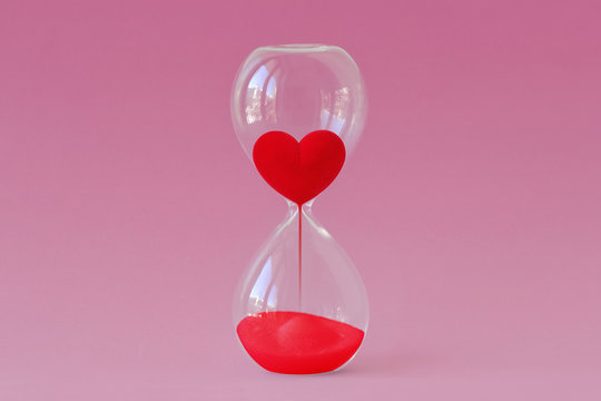 Red heart flowing in hourglass on pink background - Time for love concept