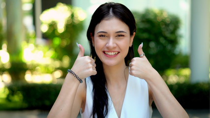 A lovely girl smiling and show thumbs up with two hands