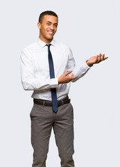 Young afro american businessman extending hands to the side for inviting to come on isolated background