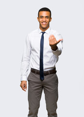 Young afro american businessman inviting to come with hand. Happy that you came on isolated background