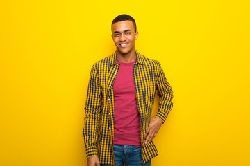 Young afro american man on yellow background posing with arms at hip and smiling