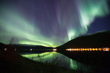 northern lights in a Fjord Norway in green, blue and violet colours and water reflexions
