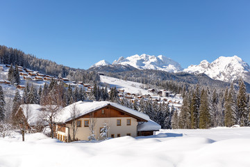 Picturesque winter scene with traditional alpine chalet and snowy alpine village on background. Sunny frosty weather with clear blue sky