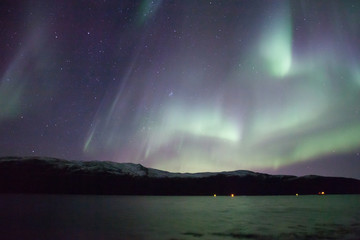 northern lights in Norway in green, blue and violet colours and mountains in the distance