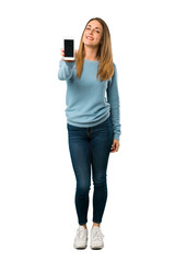 Full body of Blonde woman with blue shirt showing the mobile on white background