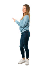 Full body of Blonde woman with blue shirt sending a message with the mobile on white background
