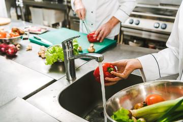Fototapeta cropped view of female chef washing pepper in restaurant kitchen obraz