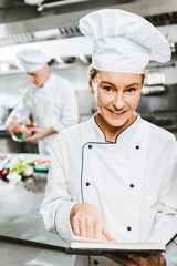 beautiful female chef in uniform holding recipe book and looking at camera in restaurant kitchen