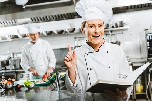 beautiful female chef in uniform holding recipe book and doing idea