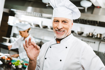 selective focus of handsome smiling male chef in uniform looking at camera and showing ok sign in restaurant kitchen