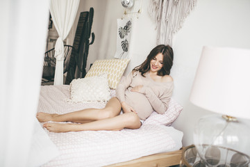 Beautiful young pregnant woman at home lying in bed