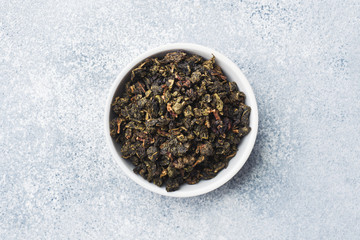 Tea leaves for brewing in bowl on a gray background.