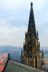 Neogothic stone tower of famous St. Vitus Cathedral on background of city, Prague, Czech Republic