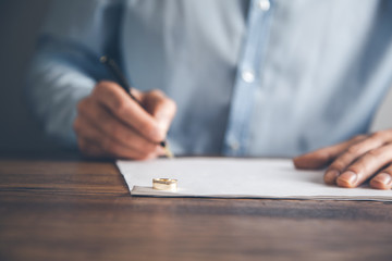 man hand document with wedding ring on desk