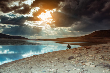 man with lake with mountain under sky