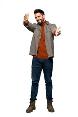 Full-length shot of Handsome man with beard presenting and inviting to come with hand on isolated white background