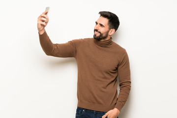 Handsome man over white wall making a selfie