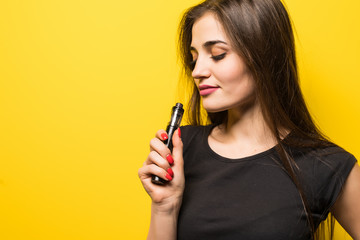 Young pretty woman with vape smoke gadget standing isolated on yellow background