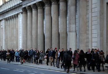 Commuters walk past the Bank of England in the City of London