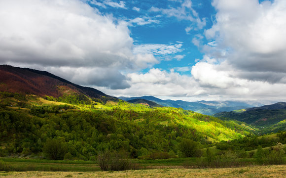 beautiful sunny morning in mountains. carpathian countryside in spring. village in the distant valley at the bottom of the ridge. cloudy sky