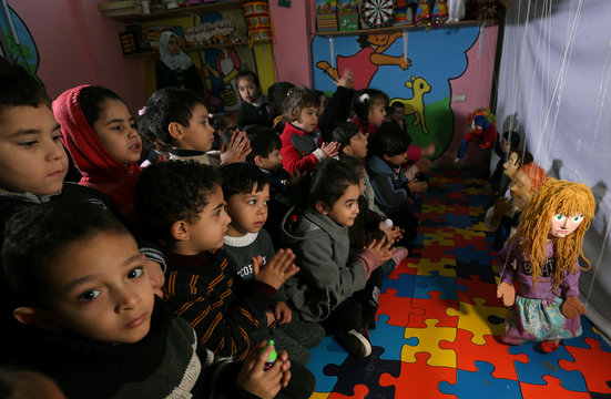 Children look at marionette puppets made by Palestinian artist Mahdi Karera, during a show at a kindergarten in Gaza City