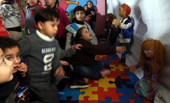 Girl plays with a marionette puppet made by Palestinian artist Mahdi Karera, during a show at a kindergarten in Gaza City