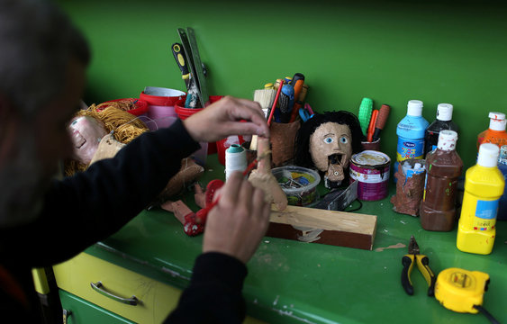 Palestinian artist Mahdi Karera makes a marionette puppet at his house balcony in Gaza City