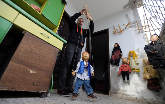 Palestinian artist Mahdi Karera holds a marionette puppet he made, at his house balcony in Gaza City