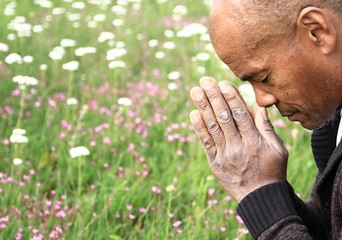 black man praying to god with hands together stock photo