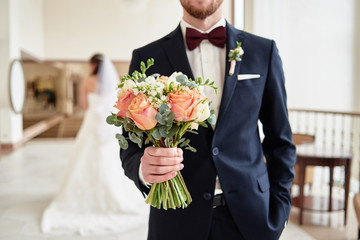 Close up of beautiful bridal bouquet of coral roses and greenery in groom's hand with bride in blur on background indoors, copy space. Happy wedding couple before ceremony