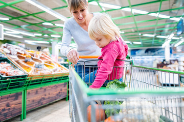 Mother having her toddler riding in shopping card of supermarket