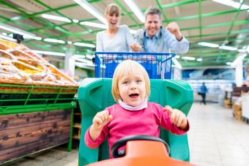 Couple shopping in supermarket using a special child trolley