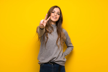 Young woman over yellow wall smiling and showing victory sign