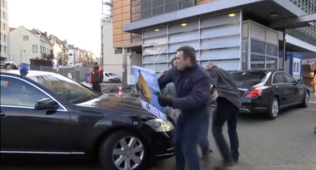 A protester tries to block a car, part of the convoy of British Prime Minister Theresa May, outside the European Commission headquarters in Brussels