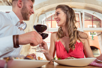 Couple on a date toasting wine glass