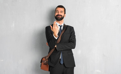 Businessman with beard inviting to come with hand. Happy that you came