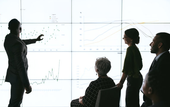 Silhouettes of black african businessman giving a presentation at a business conference to group. Large video screen with charts and graphs in front of him and team