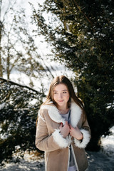 Young Beautiful girl  Smiling and posing Outdoors in Snowy Winter